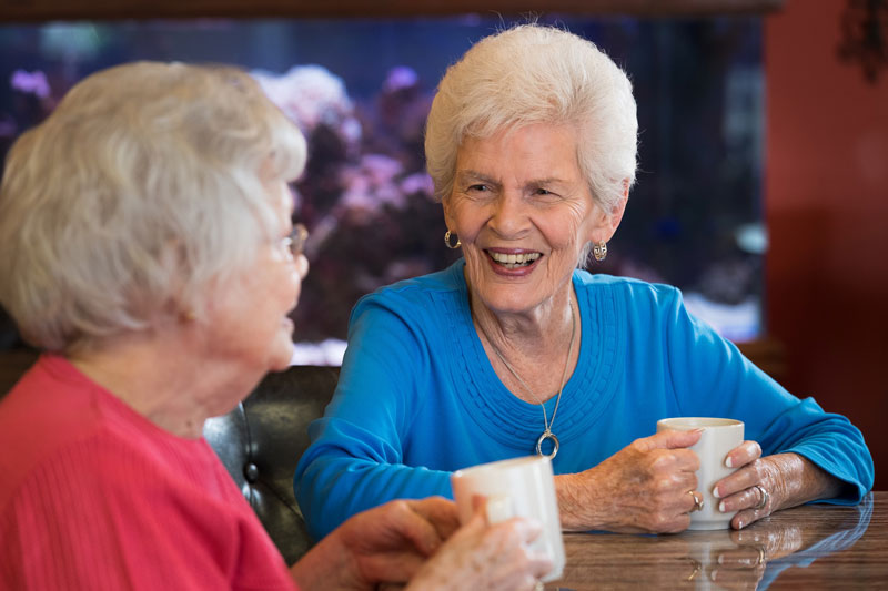 Two ladies are sitting and drinking coffee at the retirement center.t